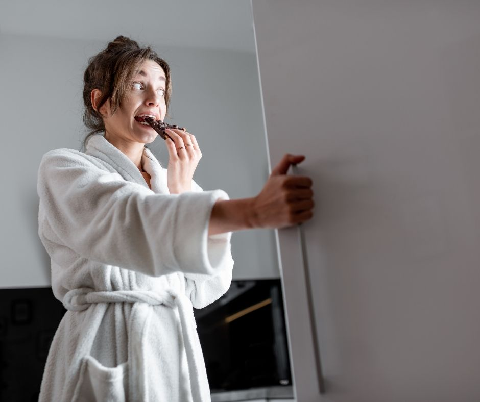 woman eating chocolate in front of fridge