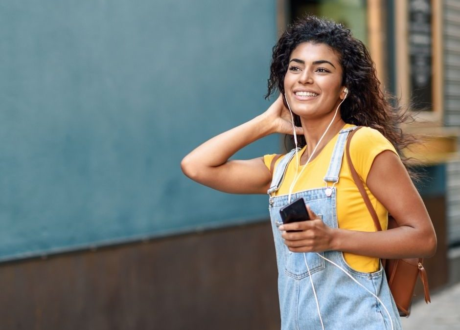 woman wearing yellow t-shirt and denim overalls listening to a podcast