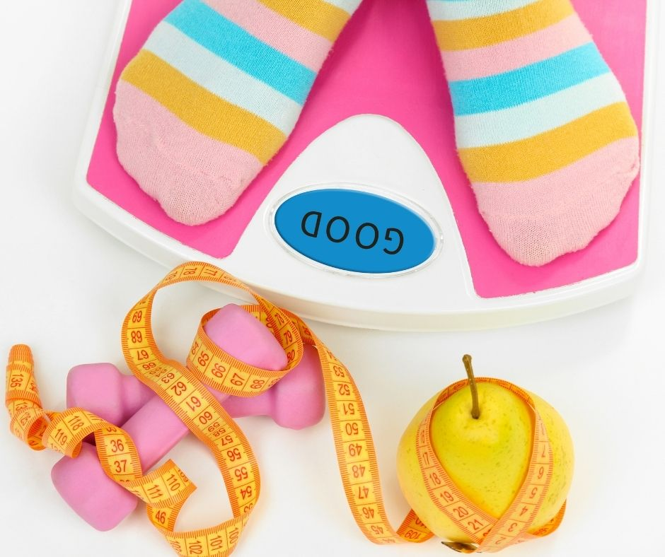 Striped socks on feet standing on scales with a tape measure, hand weights and pear